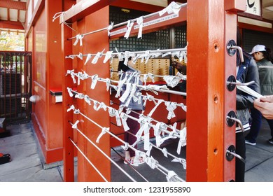 Asakusa,Tokyo - October 31 2018 : Bad luck paper predict fortune hanging tied on wire in Sensoji Temple Tokyo Japan. Japanese Language.