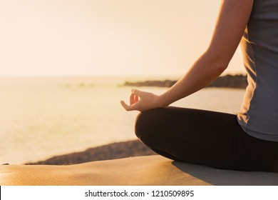 Asana lotos. Women practicing yoga at the sunset light.