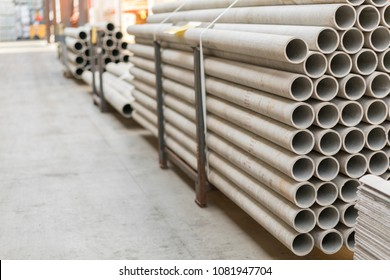 asbestos pipes in a stack in a warehouse or in a building store. Pallets with sewer pipes.