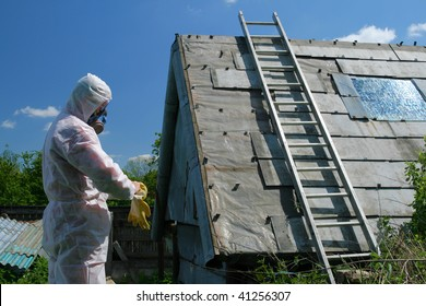 Asbestos removal worker. Dangerous waste disposal - professional works with old architecture.