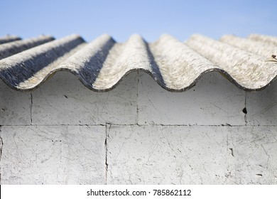 Asbestos roof above a white stone wall  - image with copy space