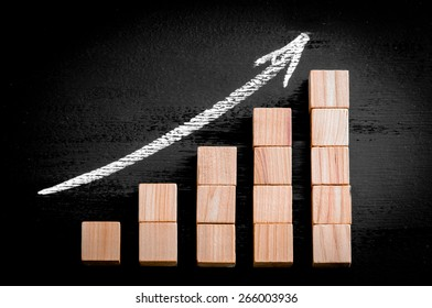 Ascending arrow above bar graph of Wooden small cubes isolated on black background. Chalk drawing on blackboard. Business Concept image.