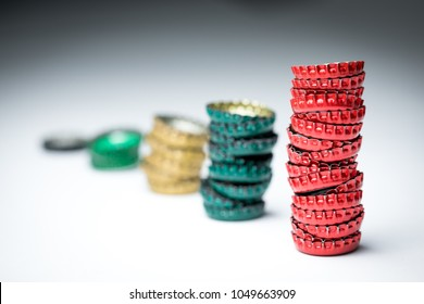 Ascending bar graph of stacked bottle caps, with focus on the tallest red stack, representing increased beer and alcohol use or soda consumption, on a black and white gradient background