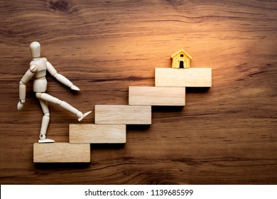 Ascending stairs and wooden man model going upward to home model isolated on wooden background. Business growth, steps to success . Go to goal, working for buy new home in future concept.