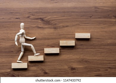 Ascending stairs and wooden man model going upward on wooden background. Business growth, steps to success or progress way to forward achievement concept.