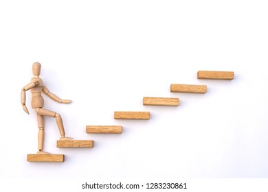 Ascending stairs and wooden man model going upward, isolated on white background.Business growth, steps to success or progress way to forward achievement concept.