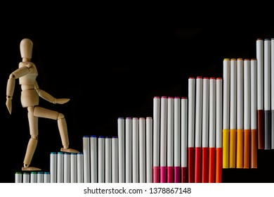 Ascending step stairs (by colorful marker pens)and wooden man model going upword isolated on dark background.Encourage motivation and inspiration to do something for success.Progression concept.