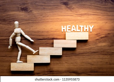 Ascending step stairs and wooden man model going upward to healthy word isolated on wooden background. Encourage and inspiration to take care yourself for healthy.
