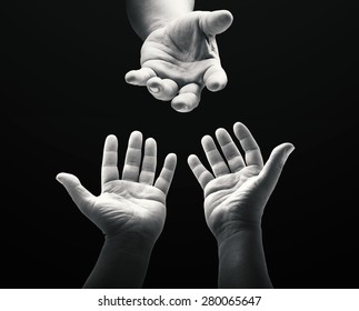 Ascension day concept: Black and white child reaching two hand to God on dark room background