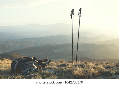 Ascent into the mountains, nordic walking sticks and a backpack, a traveler's set. Wonderful sunset in the background