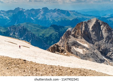 Ascent to Marmolada, Dolomites, Italy. The Marmolada Glacier. Tourist climbing on Marmolada mountain in dolomites. Ice axe in the snow. Ascending Glacier. View from the top of the mountain summit