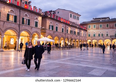 Ascoli Piceno, Italy - December 2018: People walking in winter in Piazza del Popolo, the main city square in Ascoli Piceno, Marche, Italy.