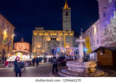 Ascoli Piceno, Italy - December 2018: People walking at night in winter in Piazza Arringo, a city square in Ascoli Piceno, Marche, Italy.