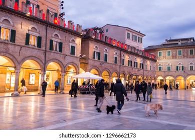 Ascoli Piceno, Italy - December 2018: People walking in winter in Piazza del Popolo, the main city square in Ascoli Piceno, Marche, Italy.