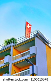 Ascona, Switzerland - August 23, 2016: House with Swiss flag at the luxurious resort in Ascona on Lake Maggiore of Ticino canton in Switzerland.