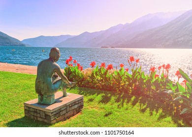 Ascona, Switzerland - August 23, 2016: Sitting woman sculpture at the promenade at the luxurious resort in Ascona on Lake Maggiore in Ticino canton in Switzerland. Sunlight toned