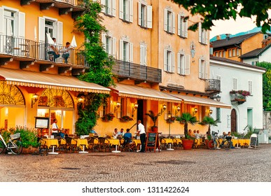 Ascona, Switzerland - August 23, 2016: People in street cafe at romantic luxury resort in Ascona town on Lake Maggiore, Ticino canton in Switzerland. Outdoor expensive family restaurants in Swiss city