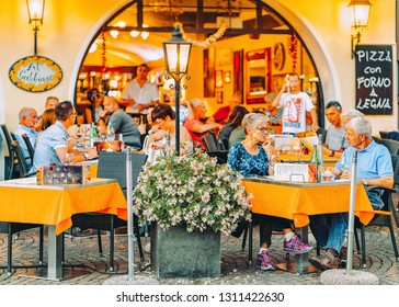 Ascona, Switzerland - August 23, 2016: Senior people in street cafe in romantic luxury resort in Ascona town on Lake Maggiore in Ticino canton in Switzerland. Outdoor expensive family restaurants