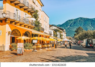 Ascona, Switzerland - August 23, 2016: People at street cafe in romantic luxury resort in Ascona town on Lake Maggiore, Ticino canton in Switzerland. Outdoor expensive family restaurants in Swiss city