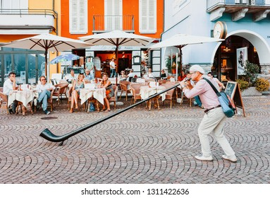 Ascona, Switzerland - August 23, 2016: Alphorn player at street cafe in romantic luxury resort in Ascona town on Lake Maggiore in Ticino canton in Switzerland. Outdoor expensive family restaurants