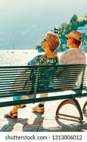 Ascona, Switzerland - August 23, 2016: Romantic senior couple sitting in bench in Ascona luxury tourist resort on Lake Maggiore in Ticino canton in Switzerland in summer. People outdoor street travel.