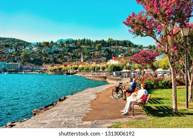 Ascona, Switzerland - August 23, 2016: Senior people sitting on bench in Ascona luxury tourist resort on Lake Maggiore in Ticino canton in Switzerland in summer. People outdoor street travel.