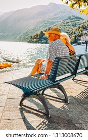 Ascona, Switzerland - August 23, 2016: Romantic senior couple sitting on bench in Ascona luxury tourist resort on Lake Maggiore in Ticino canton in Switzerland in summer. People outdoor street travel.