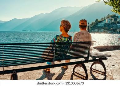 Ascona, Switzerland - August 23, 2016: Romantic senior couple sit on bench in Ascona luxury tourist resort on Lake Maggiore in Ticino canton in Switzerland in summer. People outdoor street travel.