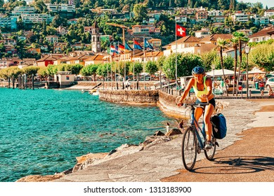 Ascona, Switzerland - August 23, 2016: Woman on bicycle in Ascona luxury tourist resort promenade on Lake Maggiore in Ticino canton in Switzerland in summer. People Swiss outdoor street travel.