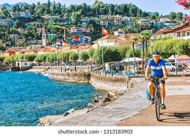 Ascona, Switzerland - August 23, 2016: Man on bicycle at Ascona luxury tourist resort promenade on Lake Maggiore in Ticino canton in Switzerland in summer. People Swiss outdoor street travel.
