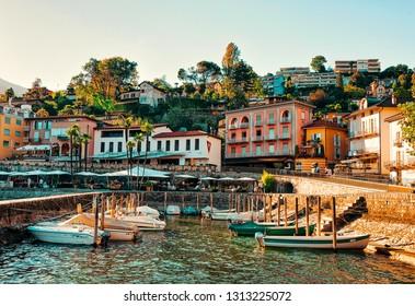 Ascona, Switzerland - August 23, 2016: Boats in Ascona luxury tourist resort promenade on Lake Maggiore in Ticino canton in Switzerland in summer. People outdoor street travel. Romantic Swiss holiday