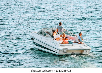 Ascona, Switzerland - August 23, 2016: Family in boat in Ascona luxury tourist resort on Lake Maggiore, Ticino canton in Switzerland in summer. Outdoor travel. Swiss holiday vacation sailing in ship