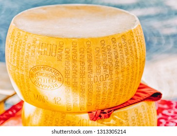 Ascona, Switzerland - August 23, 2016: Typical italian Parmigiano Reggiano cheese head on counter at Ascona. Expensive gourmet fresh food from milk. Ripe dairy traditional Swiss round product. Yellow