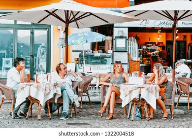 Ascona, Switzerland - August 23, 2016: People in street cafe in romantic luxury resort in Ascona town on Lake Maggiore, Ticino canton in Switzerland. Outdoor expensive family restaurants in Swiss city