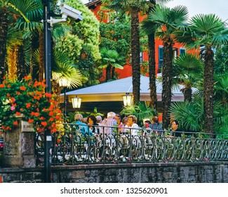 Ascona, Switzerland - August 23, 2016: Senior people in street cafe at romantic luxury resort in Ascona town on Lake Maggiore in Ticino canton in Switzerland. Outdoor expensive family restaurants