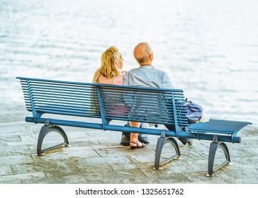 Ascona, Switzerland - August 23, 2016: Romantic senior couple sitting at bench in Ascona luxury tourist resort on Lake Maggiore in Ticino canton in Switzerland in summer. People outdoor street travel.