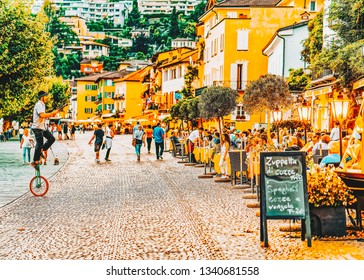Ascona, Switzerland - August 23, 2016: Senior people at street cafe at romantic luxury resort in Ascona town on Lake Maggiore in Ticino canton in Switzerland. Outdoor expensive family restaurants