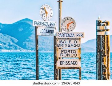 Ascona, Switzerland - August 23, 2016: Pier with clocks at Ascona luxury tourist resort on Lake Maggiore in Ticino canton in Switzerland in summer. Cities and towns name on plates. Outdoor travel