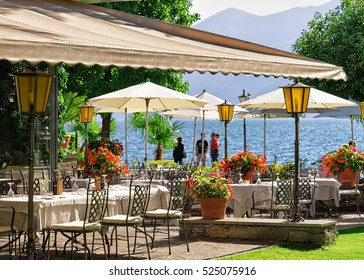 Ascona, Switzerland - August 23, 2016: Typical restaurant terrace with chairs and tables ready for a meal at the expensive resort in Ascona on Lake Maggiore of Switzerland. Peope on the background