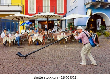 Ascona, Switzerland - August 23, 2016: Alphorn player entertaining people at the restaurant in Ascona on Lake Maggiore, Ticino canton, Switzerland.