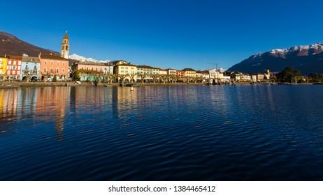 Ascona, Switzerland - December 2013: luxury tourist resort promenade on Lake Maggiore in Ticino canton in Switzerland in summer. People outdoor street travel. Romantic Swiss holiday