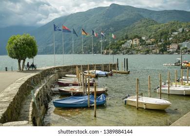 Ascona, Switzerland - September 2, 2018: People sitting on bench near small port on Lago Maggiore in Ascona, Switzerland during still summer day 2018