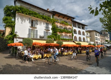 Ascona, Switzerland - September 2, 2018: Cyclists driving next to open restaurant on the promenade in Ascona, Switzerland during beautiful sunday in summer 2018