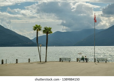 Ascona, Switzerland - September 2, 2018: Two people sitting on the bench on Lago Maggiore shore in Ascona, Switzerland during windy summer day 2018