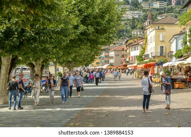 Ascona, Switzerland - September 2, 2018: People walking through promenade next to lake Maggiore in Ascona, Switzerland during sunny day in 2018