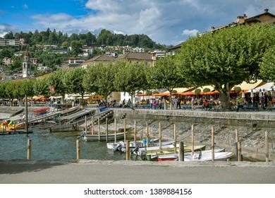 Ascona, Switzerland - September 2, 2018: People enjoying day near lake in Ascona, Switzerland during sunny and windy day in September 2018