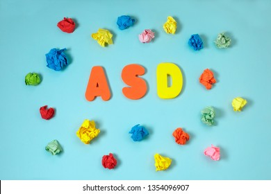 ASD. Autism spectrum disorder from color letters surrounded by scattered colorful crumpled paper on blue background. World Autism Awareness Day, April Autism awareness month