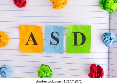 ASD. ASD (Autism spectrum disorder) on notebook sheet with some colorful crumpled paper balls around it. Close up.