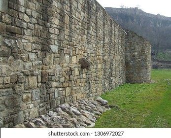 Asenovo district, Veliko Tarnovo, Bulgaria - February 2018: Mighty stone wall surrounding the Holy Forty Martyrs church, with a lion head in it and fortress walls in background