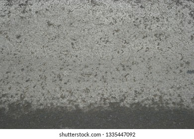 Asfalt surface background with line of wet surface beneath